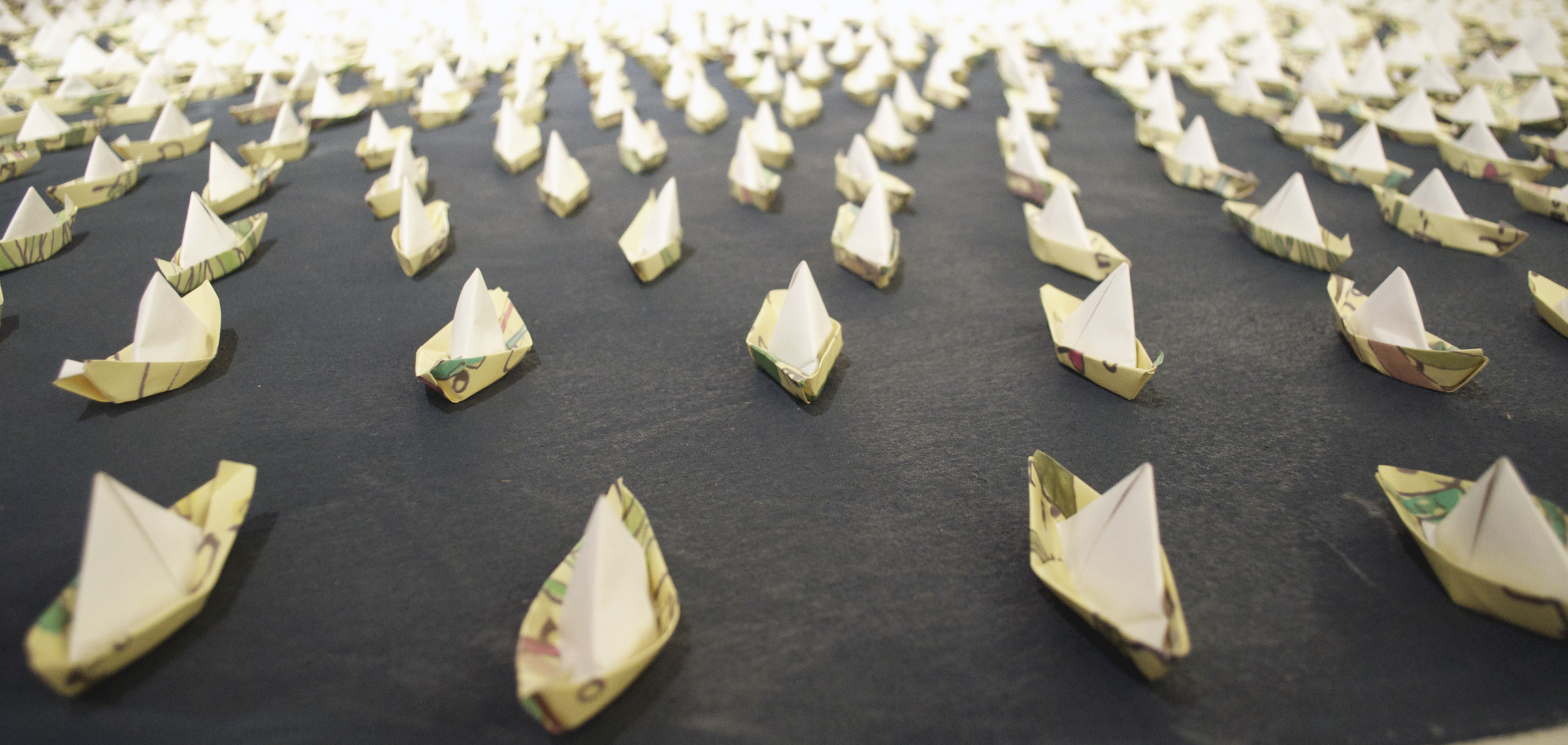 Origami boats on painted canvas